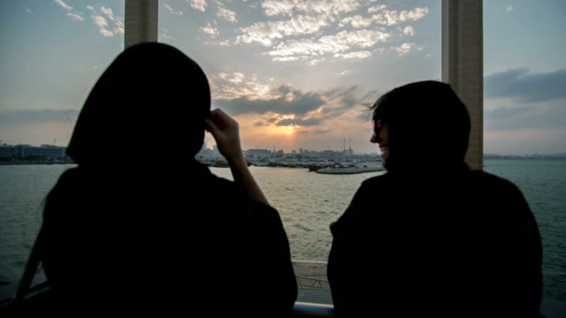 Two women in flowing abayas are looking from the Museum of Islamic Art in the direction of Doha City, Qatar.