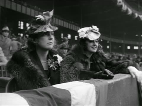 two women in furs + hats sitting in stadium / lou gehrig's farewell - 毛皮のコート点の映像素材/bロール