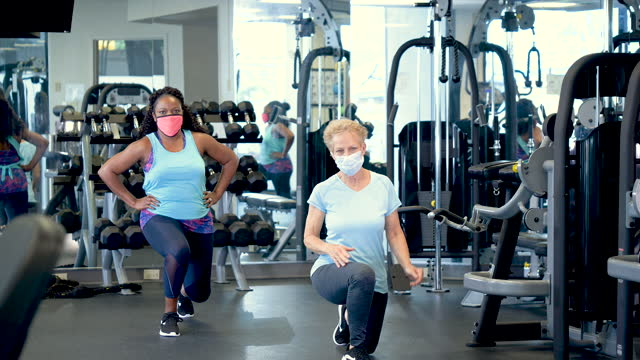 two women in gym doing lunges, wearing face masks. - gulf coast states stock videos & royalty-free footage