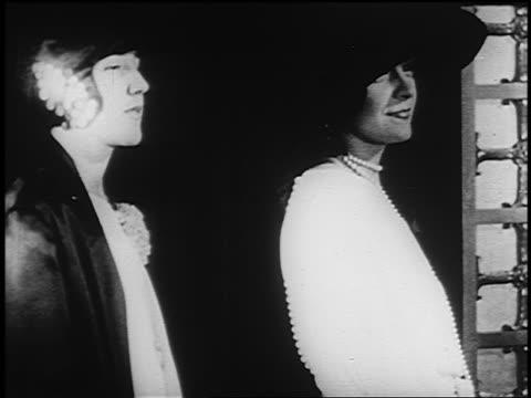 vídeos y material grabado en eventos de stock de b/w 1926 two women in hats turning to camera + smiling - 1926