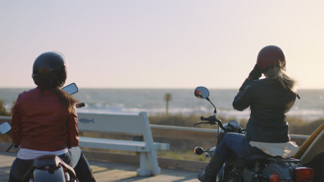 SLO MO. Two women in leather jackets on motorcycles pull helmets on overlooking the ocean.