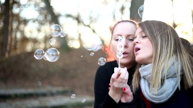 due donne innamorate che fanno bolle di sapone - altruismo video stock e b–roll