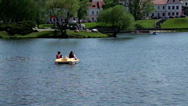 Two women in pedal boat on the lake in city park