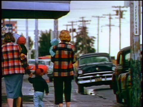 1957 rear view two women in plaid jackets walking with children + baby on sidewalk - 1957 stock-videos und b-roll-filmmaterial