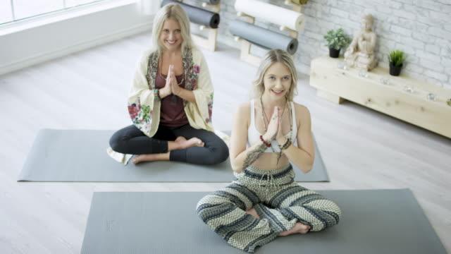 vídeos de stock, filmes e b-roll de duas mulheres em pose de oração - tatame equipamento para exercícios