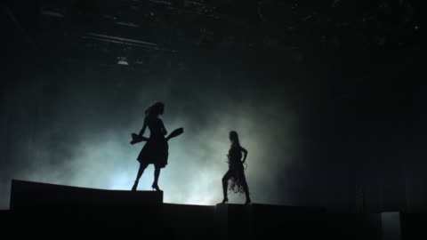 two women in silhouette standing on a stage with wind blowing into their hair and dress. - attityd bildbanksvideor och videomaterial från bakom kulisserna