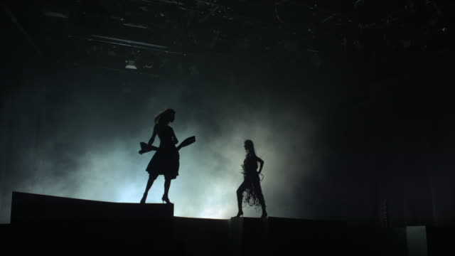 Two women in silhouette standing on a stage with wind blowing into their hair and dress.