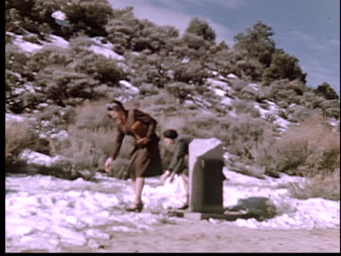 1946 FILM MONTAGE MS Two women in skirts on side of mountain throwing snowballs/ California