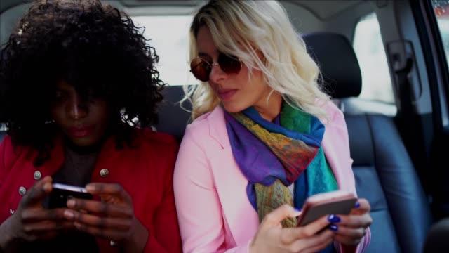 vídeos y material grabado en eventos de stock de dos mujeres en el asiento trasero en el taxi hablando durante el uso de teléfonos móviles - de lado a lado