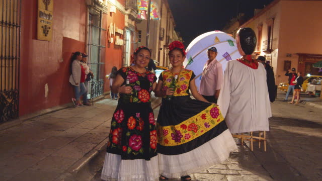 two women in their colorful traditional attire and holding mezcal bottles pose for a photograph during calenda celebration in oaxaca, mexico. - puppet stock videos & royalty-free footage