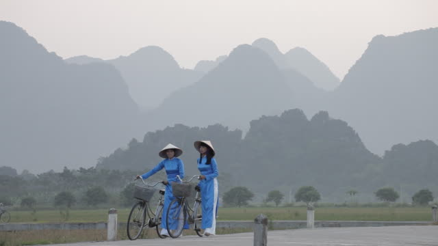 two women in traditional dress walk along a road while pushing their bicycles near hanoi, vietnam. - traditional clothing stock videos & royalty-free footage