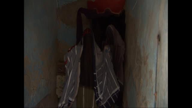 two women in traditional full-length burkas walk through a hallway and exit a building. - モデスト・ファッション点の映像素材/bロール