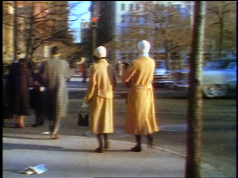 1957 rear view two women in yellow coats walking on city sidewalk / feature - 1957 stock-videos und b-roll-filmmaterial