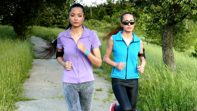 two women jogging in the forest-slow motion - arm band stock videos & royalty-free footage
