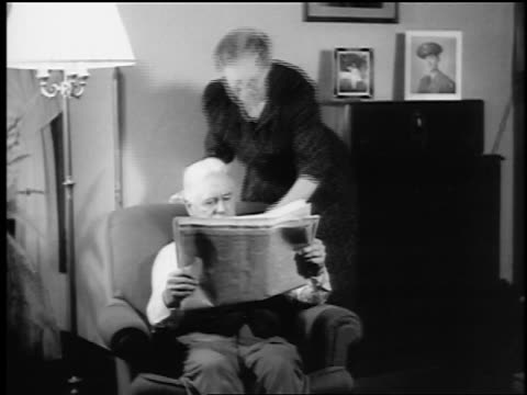 B/W 1943/44 two women join senior man reading newspaper in chair in living room / newsreel