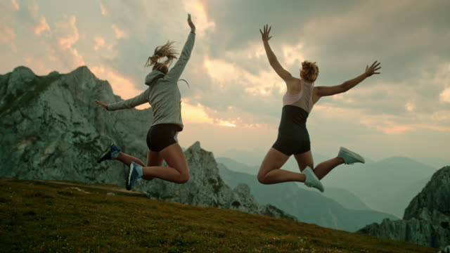 slo mo two women jumping in joy on the top of a mountain - punching the air stock videos & royalty-free footage