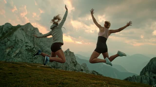 stockvideo's en b-roll-footage met slo mo twee vrouwen jumping in vreugde op de top van een berg - julian alps