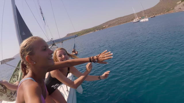 vídeos de stock e filmes b-roll de two women jumping off a sailboat and swimming underwater in greece. - slow motion - vela desporto aquático