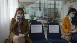 Two women keeps social distancing at bank waiting room