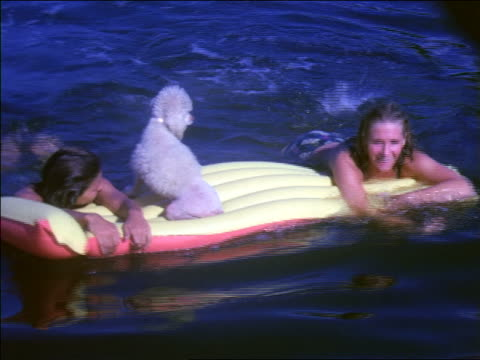1966 two women kicking legs on inflatable raft with poodle in lake / home movie