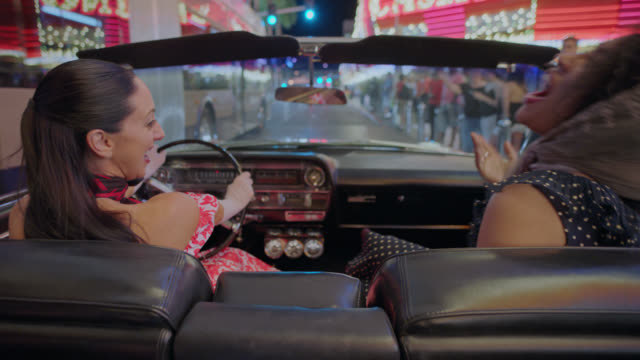 Two women laugh as they drive through downtown Las Vegas in a classic convertible.