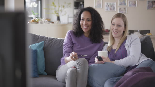 two women laughing while watching tv and eating ice cream - ice cream stock videos & royalty-free footage