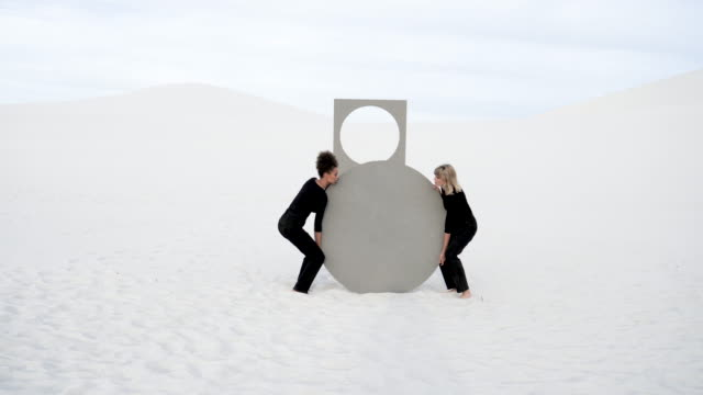 two women lift circular portal in desert - picking up stock videos & royalty-free footage