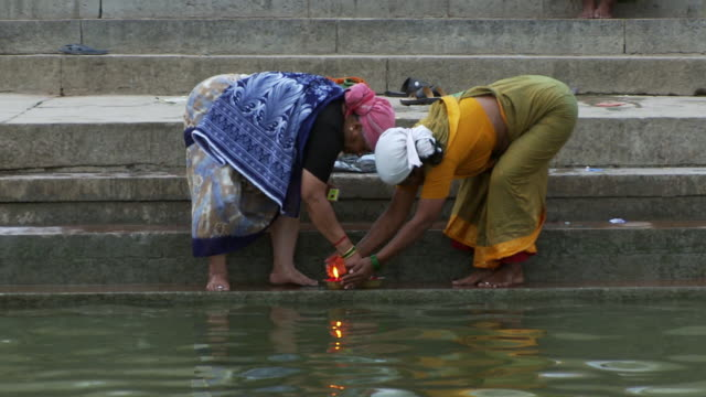 Two women lighting floating candles