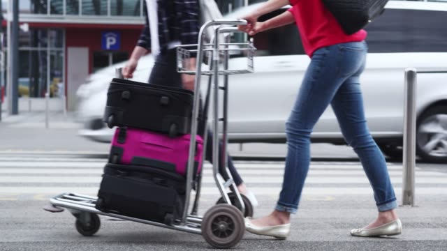 two women loading luggage onto trolley - push cart stock videos & royalty-free footage