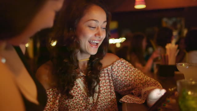 stockvideo's en b-roll-footage met two women look at a mobile phone in a salsa club / medellin, colombia - bar tapkast