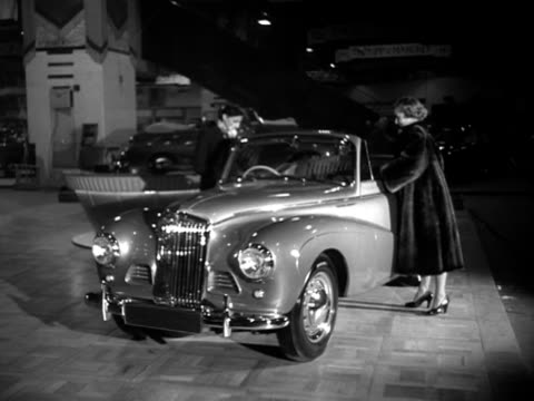 two women look at a sunbeam talbot at the earls court motor show. - earls court stock videos & royalty-free footage