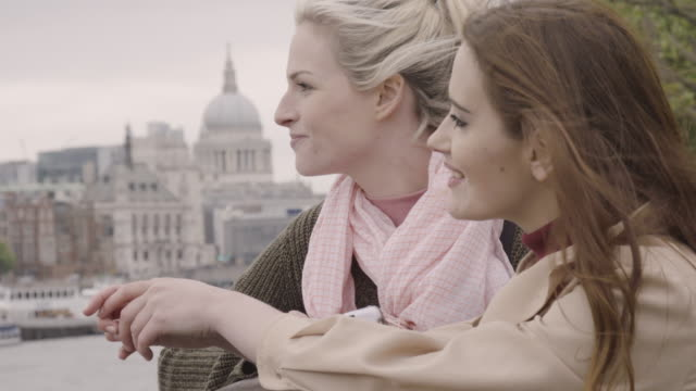 Two women look out over the river Thames with the st Pauls cathedrale in the background.