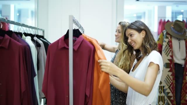 stockvideo's en b-roll-footage met twee vrouwen op zoek naar business kostuums in een kledingwinkel - kledingrek