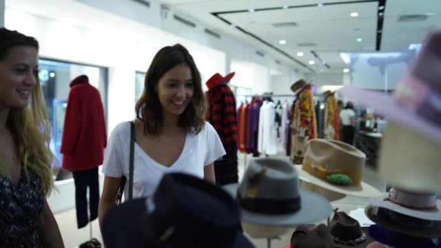 two women looking at hats in a clothing store - cappello video stock e b–roll