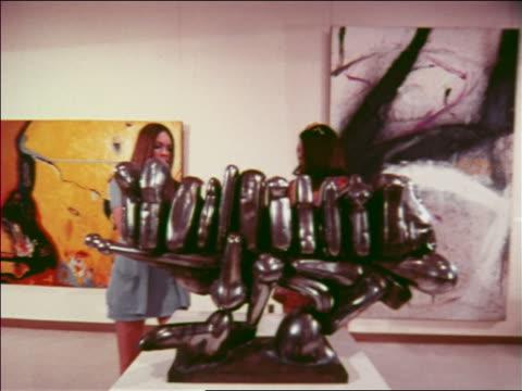 1970 two women looking at metal sculpture in art museum / atlanta / travelogue - ausstellung stock-videos und b-roll-filmmaterial