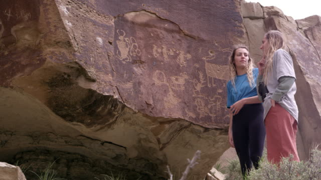 vídeos de stock, filmes e b-roll de two women looking at petroglyph panel on cliff discussing what they see - anasazi