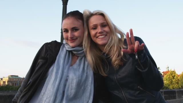 vídeos de stock, filmes e b-roll de two women looking at the camera and smiling - ponte carlos