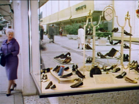 1962 two women looking in shoe store display window then entering store / industrial