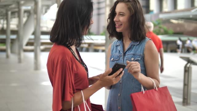 2 人の女性が通りに買い物袋を持つスマート フォンに探して - 買い物袋点の映像素材/bロール