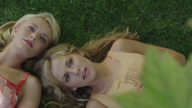 two women lying on the grass