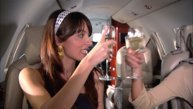 MS two women making champagne toast on private jet