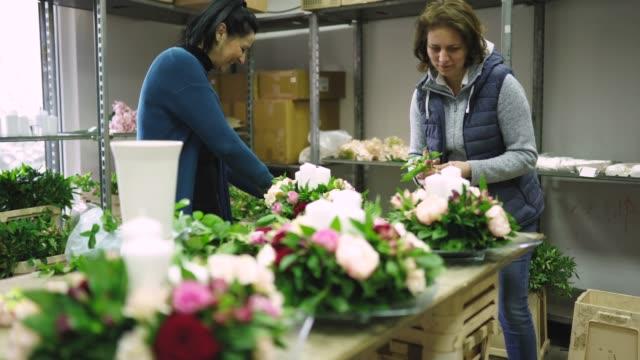 two women making floral arrangement for wedding - flower arrangement stock videos & royalty-free footage