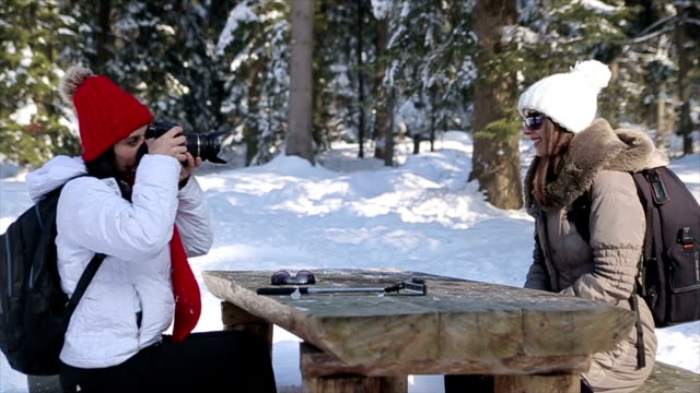 two women making pictures and memories from a winter vacation - ski jacket stock videos and b-roll footage