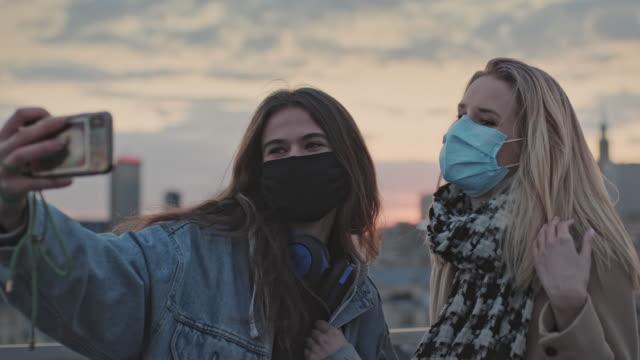 due donne che fanno selfie su un tetto. tramonto in città durante la pandemia - casacca video stock e b–roll
