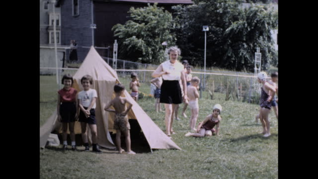 vidéos et rushes de two women managing group of kids dressed in swimwear playing on the lawn; couple of kids posing in front of small tent and houses in the background - tente