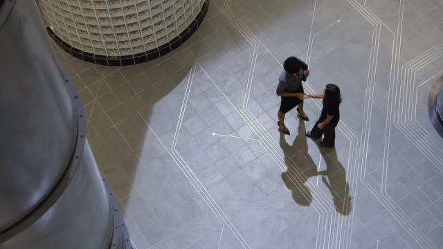 WS PAN Two women meeting in office hallway / Orem, Utah, USA