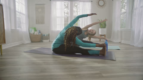 slo mo. two women mirror each other's movements with seated side stretches in home yoga studio. - stretching stock videos & royalty-free footage