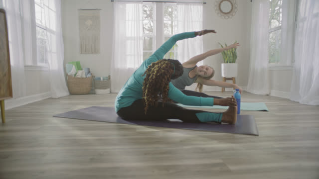 vídeos y material grabado en eventos de stock de slo mo. two women mirror each other's movements with seated side stretches in home yoga studio. - ejercicio físico