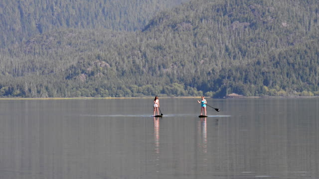 Two women navigate stand up paddle boards on ocean bay