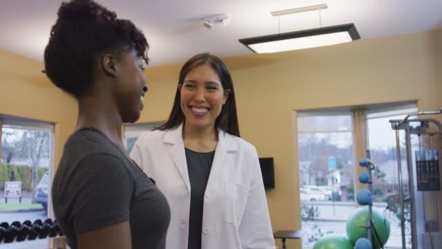 vídeos y material grabado en eventos de stock de dos mujeres de color en una clínica de terapia física - fisioterapia deportiva